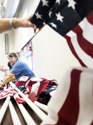 Debbie Griffis, of New Oxford, passes down a flag pole during the Flag Assembly for the Fifteen Year 9/11 Healing Field event Saturday at the West Manheim Township building. The event will be on display Sept. 9-17 at the West Manheim Elementary School. Amanda J. Cain photo