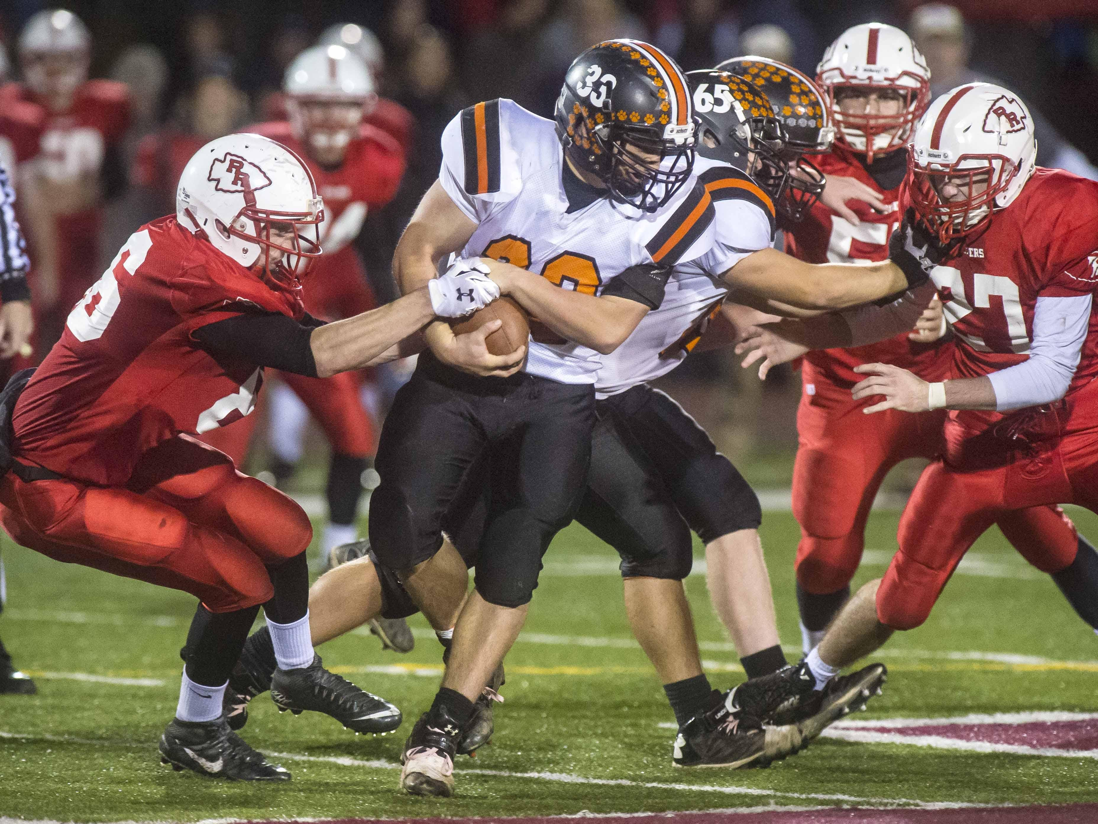 Rutland's Austin O'Gorman, left, tries to strip the ball from Middlebury's Cortland Fischer in the D1 state football championship in Rutland on Saturday, November 7, 2015.