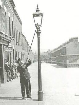 A lamplighter using a long pole to extinguish a street lamp.