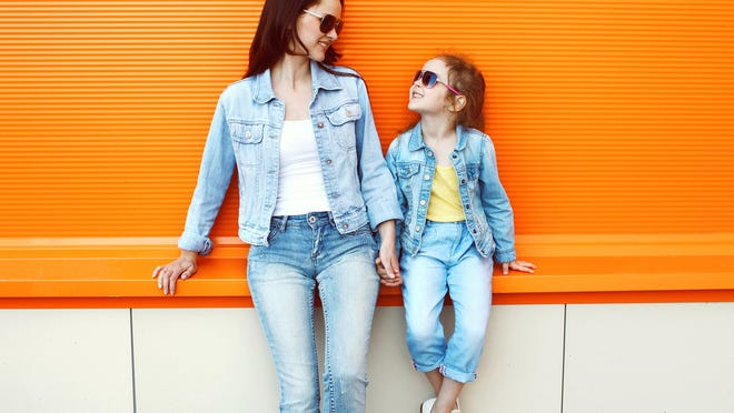 A mother and daughter wearing sunglasses and denim.