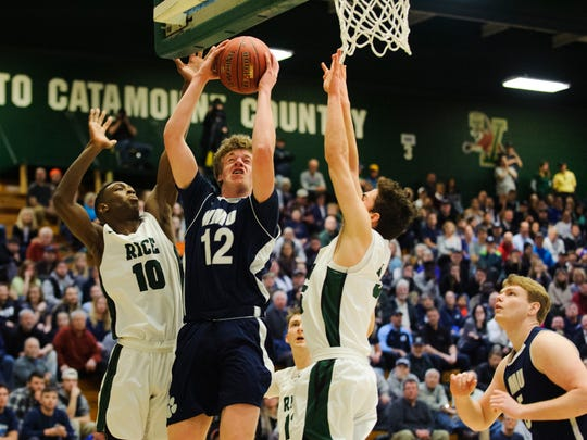 MMU's Asa Carlson (12) leaps for a lay up past Rice's Leo Chaikin (10) during the Vermont state division I boys basketball semifinal game between the Mount Mansfield Cougars and the Rice Green Knights at Patrick Gym on Thursday night March 15, 2018 in Burlington.