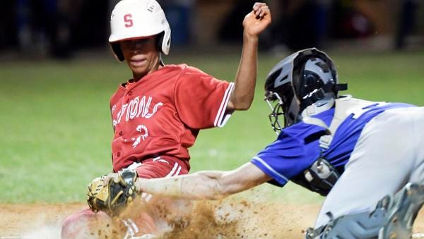 Satellite's Isaac Lopez is tagged out at the plate by Titusville catcher Eric Sellers during Friday's District 9-5A championship.