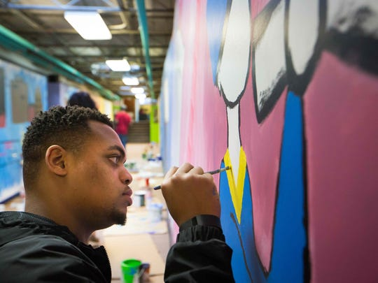 Justin Hill paints a mural at Kingswood Community Center as part of a Martin Luther King Jr. Day commemoration.