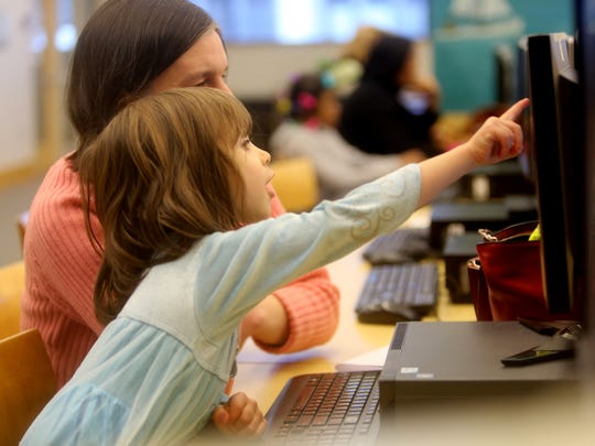 Clare Detko of Ossining and her niece Elizabeth, 4, play on a computer at the Yonkers Public Library's Riverfront branch Feb. 13, 2016. The two were visiting the Yonkers library to see a family member perform in the library's auditorium, and took a break to spend time on the computer.