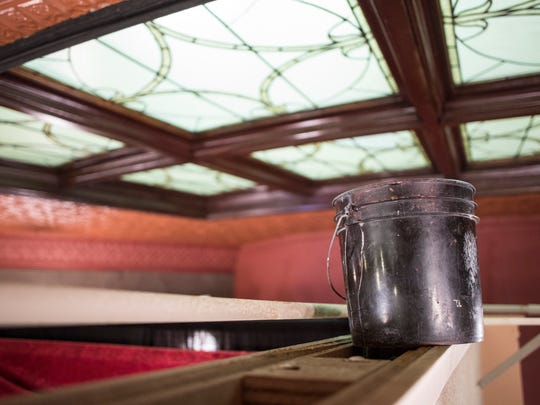 A bucket catches water dripping from a ceiling at the