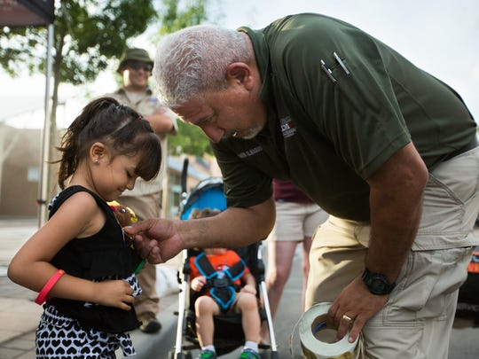 Three-year-old Jazlynn Lucero, left, receives an Office of Emergency Management sticker from Emergency Management Supervisor David Almaguer during National Night Out  in Las Cruces. Almaguer advises proactive planning  for a variety of possible emergencies.