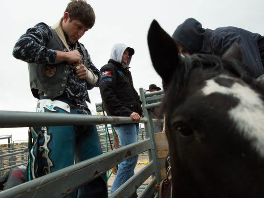 Trenten Montero, left, prepares to saddle up on a saddle