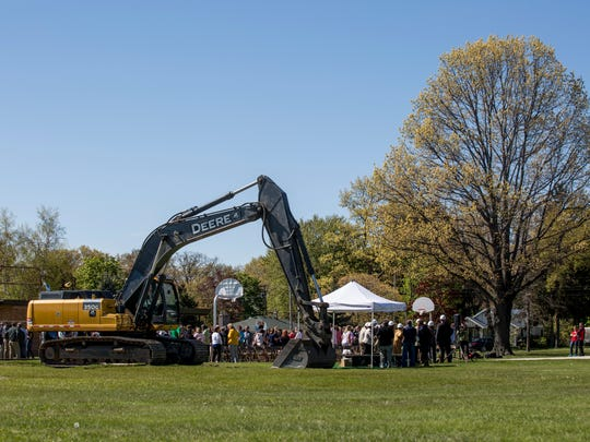 Dozens of people gather during a groundbreaking ceremony
