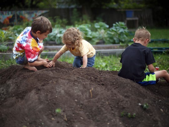 In a Saturday, Sept. 2, 2017 photo, Rudi Petruziello, 6, left, Corinne Petruziello, 2, center, and Darren Eaton, 6, right, play on a mound of soil during a tour of Glass City Goat Gals, which is part of the Ohio Sustainable Farm Tour and Workshop Series in Toledo, Ohio. Glass City Goat Gals owner Liz Harris has spent seven years transforming an area that once consisted of 15 abandoned homes — before the Lucas County Land Bank tore them down — into an urban farm on Mentor Drive promoting wellness, healthy eating, and environmental sustainability.