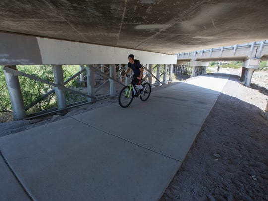 A bicyclist rides under Main Street along the Out Fall Channel Trail which runs along an arroyo. With the help of the $35.6 million GO Bond the city wants to finish connecting Out Fall Channel Trail to La Llorona Trail along with other park improvements. Friday July 20, 2018.