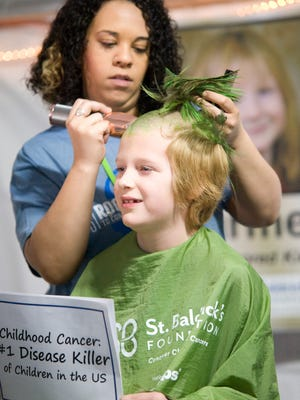 A trimmer holds the green mohawk that Liam Turner sported before taking part in the 2019 St. Baldrick's cancer fundraiser at BW3 in Alliance.
