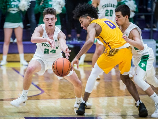 New Castle's Nicholas Grieser, left, plays defense on Marion's Jalen Blackmon in their regional championship game at Marion High School Saturday, March 10, 2018.