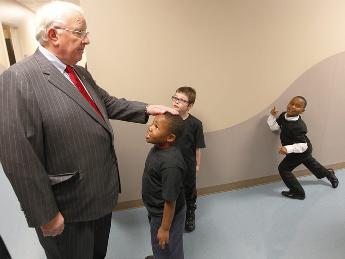 Mayor Thomas Richards, left, stops in the hallway to chat with children, from left, Dennis Welch, Chasin Gallaway, both 7, and Zavian Curry, 6, all of Rochester, on his way to a ribbon-cutting ceremony and open house to celebrate completed renovations at the David F. Gantt Community Center on Dec. 20, 2013.