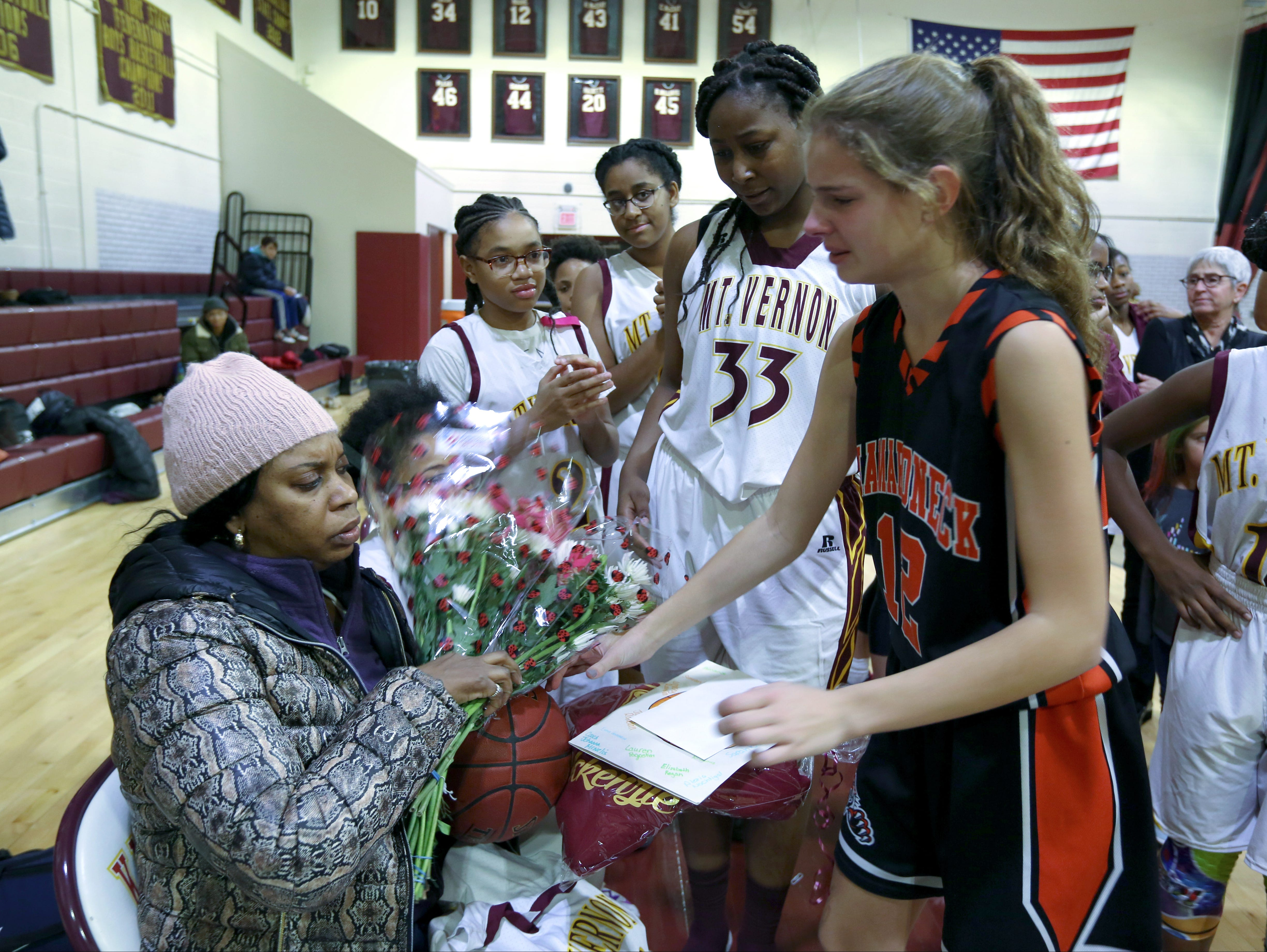 Nadine McKenzie receives flowers before the Mamaroneck at Mount Vernon junior varsity basketball game at Mount Vernon Jan. 6, 2017. Her daughter, Shamoya McKenzie, 13, a member of the Mount Vernon team, was killed by a stray bullet on New Year's Eve.