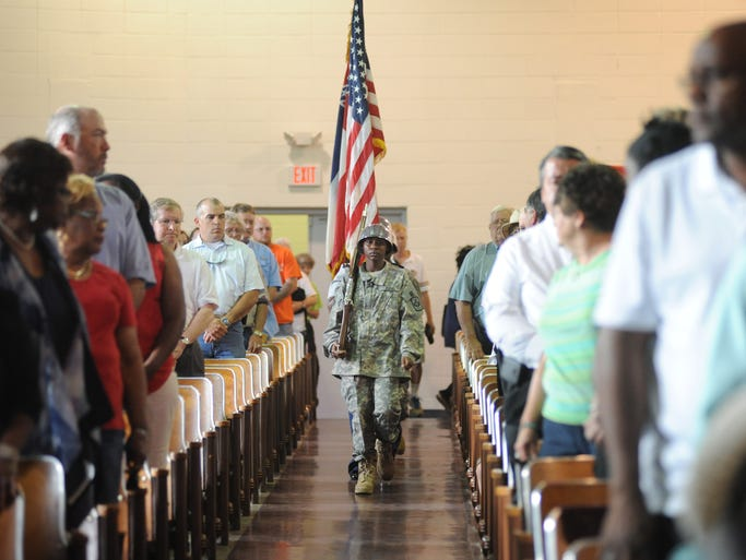 The crowd in attendance stands at as a color guards presents colors to open a memorial service at Louisville High School on Sunday in remembrance of victims of the tornado that devastated parts of Winston County on April 28 and claimed 10 residents' lives.