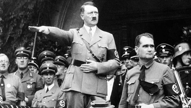 This file photo from December 30, 1938, shows German Chancellor Adolf Hiter, his personal representative Rudolf Hess, right, and German Minister of Propaganda Dr. Joseph Goebbels, left, during a parade in Berlin, Germany in 1938.