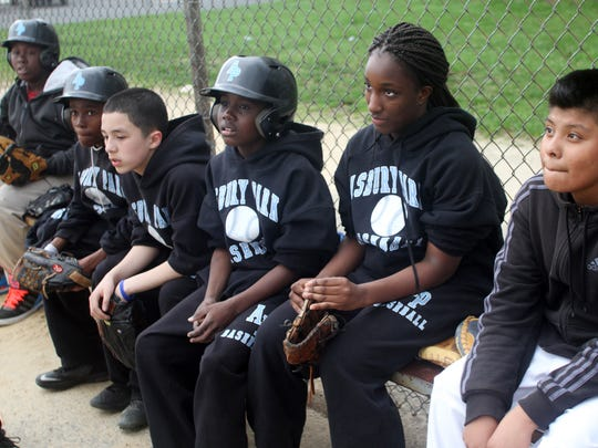 Asbury Park Middle School baseball player Nalah Tinsley (second from right) sits with her teammates during a recent practice.