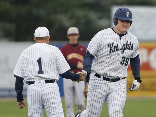 FILE – Central Catholic coach Tim Bordenet congratulates Coy Cronk after Cronk's solo homer tied the game 1-1 with McCutcheon May 9, 2016.