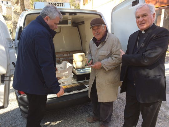 Monsignor Konrad Krajewski, right, stands with a cheese maker in Camerino, central Italy, Wednesday, Feb. 23, 2017.  Pope Francis's chief alms-giver is on a shopping spree in quake-struck central Italy, buying up prosciutto, cheese and local produce from struggling local businesses and donating the bounty to Roman soup kitchens.