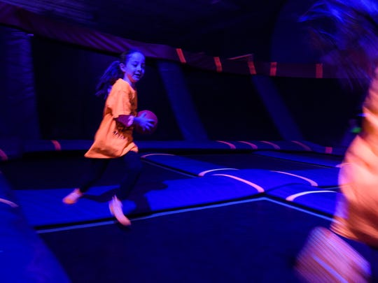 Jordan Thompson, 5, (left) chases her twin sister Mila Thompson around a dodgeball trampoline court during the GLOW Jump at Sky Zone in Evansville, Ind., Sunday, Dec. 31, 2017.