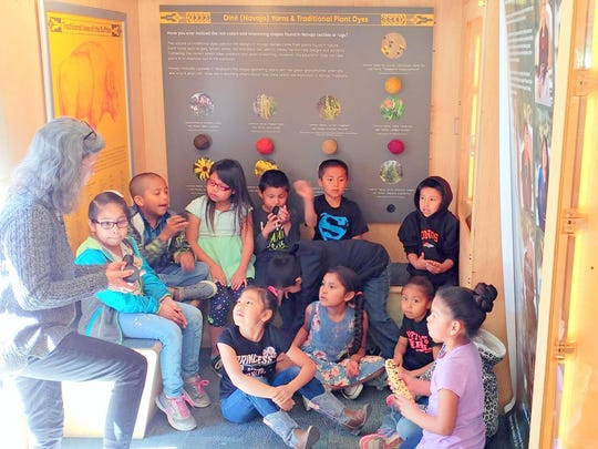 Students from Caverly Smith's first-grade class listen while touring
