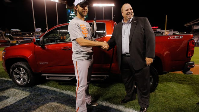 Chevrolet official Rikk Wilde congratulates San Francisco Giants pitcher Madison Bumgarner after awarding him a 2015 Colorado truck.