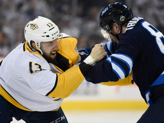 Nashville Predators center Nick Bonino (13) fights with Winnipeg Jets defenseman Jacob Trouba (8) during the third period of Game 3 in the second-round NHL Stanley Cup playoff series at Bell MTS Place in Winnipeg, Manitoba, Canada, Tuesday, May 1, 2018.