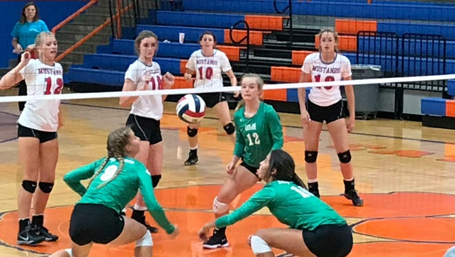 The Wall Lady Hawks work together to dig the ball and try and set up their offense against Midland Christian at the Nita Vannoy Memorial Volleyball Tournament in August.