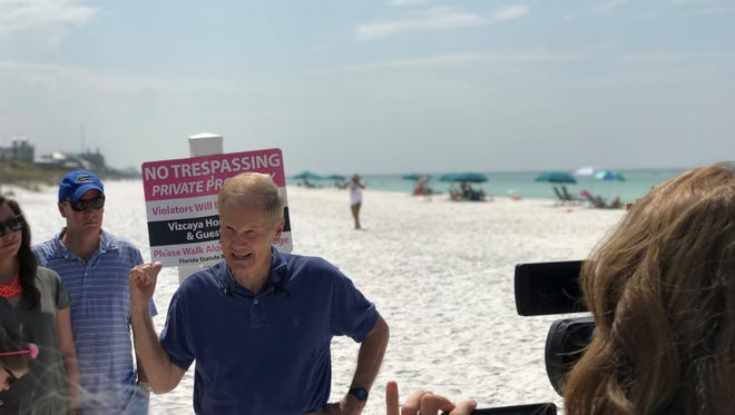 """Sen. Bill Nelson talks to constituents on the beach, in front of a """"No Trespassing"""" sign."""
