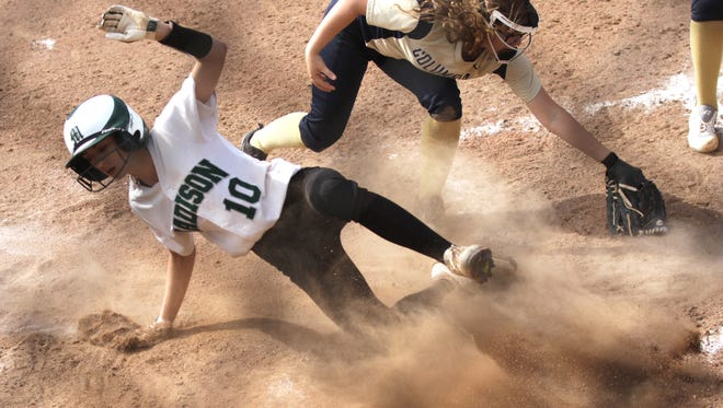 Madison's Leah Boggs scores a run while sliding into home plate while playing in the division II district tournament against Columbian High School at Milan on Wednesday.