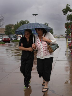 Rylie and Debi Jo Cass huddled under an umbrella Tuesday while leaving King Sooper grocery store. This week is expected to be drier and warmer as monsoon rains leave the Windsor area.