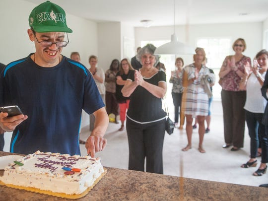 Louis Lopez cuts his birthday cake in his new home after a ribbon-cutting ceremony Wednesday that welcomed Lopez and his mother, Elida Echevarria, into their new home.