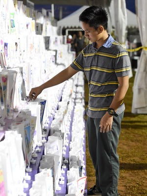 Anthony Dela Cruz of Dededo tends to the luminaria on display at the American Cancer Society Relay for life at the George Washington High School track on May 29.  