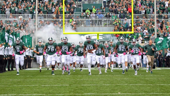 Coach Mark Dantonio, right, and MSU's seniors lead the Spartans onto the field before their game against Indiana on Oct. 24.