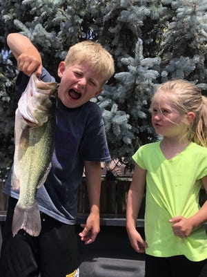 Jace painfully holds a big bass while his sister Dani watches.