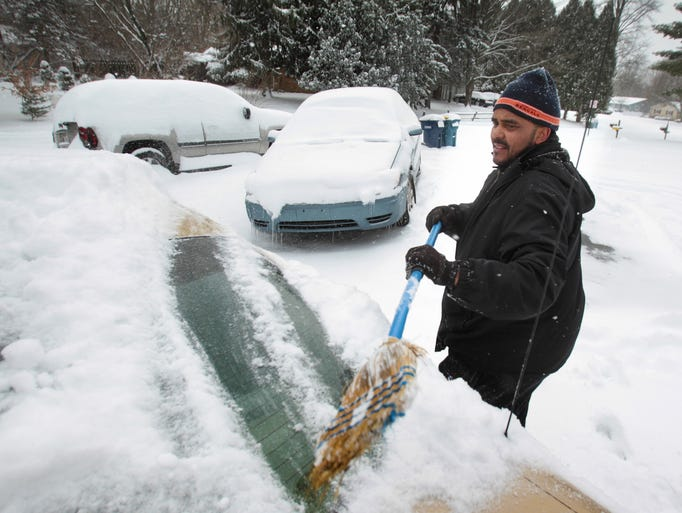 John Michaels uses a worn broom to clean snow off his car in the 1600 block of West 72nd Street, off of Grandview Avenue, after a heavy snow fell in Indianapolis on January 2, 2014.