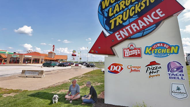 Dave Hulting, left, 60 of Moline, sat in the shade with his great nephew Jay Schaeffer, 19 of Phoenix, at the Iowa 80 Truckstop, billed as the world's largest, located at the Walcott exit.  With them is Dave's dog Winnie, a shitzpoo.