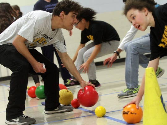 Children and young adults play a game during a Buddy Ball Program, Wednesday, December 2, 2015, in the gymnasium at the Piscataway Board of Education.