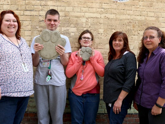 A contingent from the SK Schools Community Transition Program included Karla Canida, from left, students Dylan and Beth, job coach Theresa Worcester and teacher Tamma Terry. The program is selling paw-print pavers to raise money for outings.