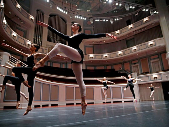 Dancers leap across the stage in a master class taught