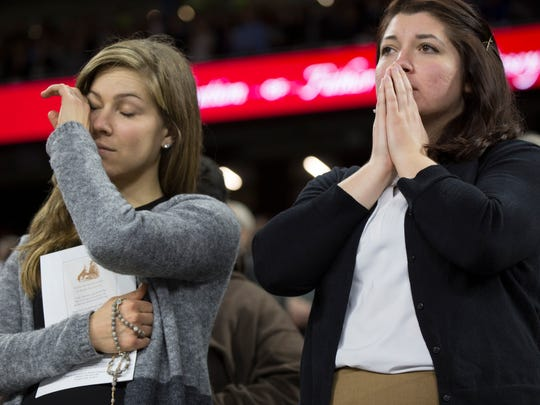 Two audience members become emotional during Saturday's ceremony that celebrates the beatification of Father Solanus Casey, Saturday Nov. 18, 2017 at Ford Field in Detroit.