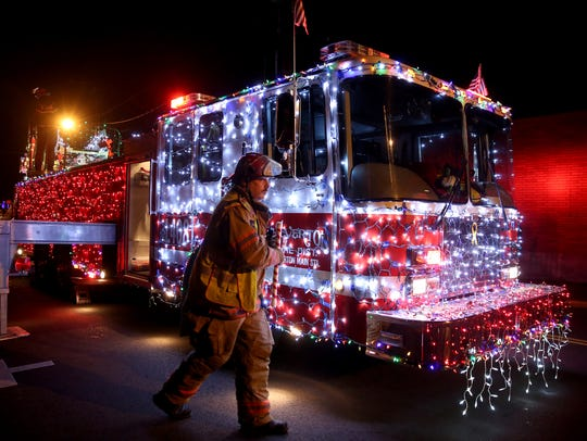 A Silverton firefighter walks past a fire engine covered in lights during the 2017 Silverton Tree Lighting Ceremony at Town Square Park.
