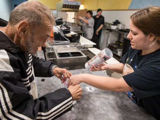 "Larry ""The Can Man"" VanNess collects pop tabs from Brandy Pruitt at a diner in Anderson, Ind., Monday, Nov. 20, 2017. The 70-year-old Anderson man began collecting tabs for Ronald McDonald House Charities of Central Indiana in 2003 and is working on his 16th million. Many businesses and people in Anderson and across the state give tabs to VanNess to help his cause. ""It's not just one person, it's a family,"" VanNess said."