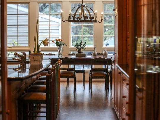 A large kitchen with a pewabic tile backsplash, large kitchen island, and craftsman-style cabinets opens up to a large breafast table in this original 1926 Coryell Homestead residence in a historic neighborhood of Birmingham, Mich., photographed on Tuesday, Jan. 23, 2018.