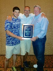 Crown Trophy founder Chuck Weisenfeld, center, presents Brandon Gano, left, and Jim Gano, right, with the Crown Trophy Sales Achievement award.