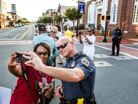 Dawn Broughton takes a selfie with police Officer Russ Michaud following a vigil and march through Middletown on Thursday evening. About 100 Middletown residents gathered in the town's Cochran Square for a prayer vigil and unity march.