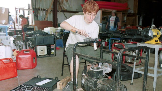 Ron Clark cleans an engine head of a generator at Tanks-A-Lot in Tamuning in July 2002.