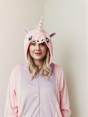 Playful woman in unicorn costume.
