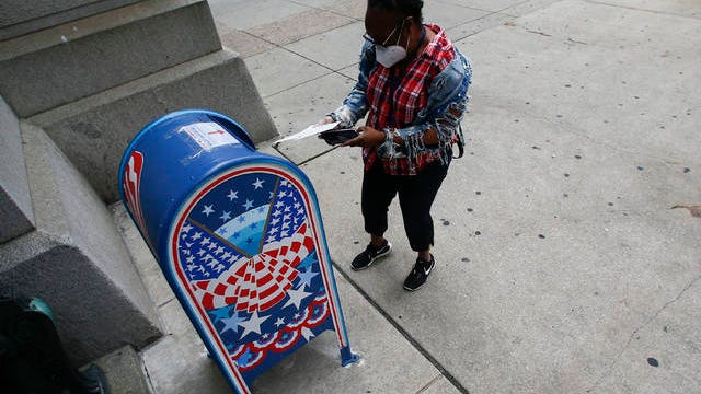 A voter prepares to drop off a ballot at a drop box outside Philadelphia City Hall on May 28. Yong Kim/The Philadelphia Inquirer/TNS