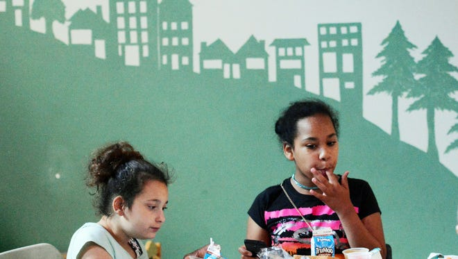 Laticha Santiago, 8, left, and Grace Mitchell, 11, both of York City, eat lunch in the shadow of a hillside mural during the Summer Food Service Program at Martin Library Tuesday, July 11, 2017. The program offers free breakfast and lunch to children 18 and younger Monday through Friday. Bill Kalina photo